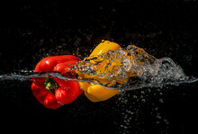 Red And Yellow Pepper Splash Into Clear Water