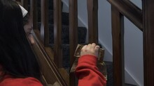 Young Girl Teenager Sticking Double Christmas Bows With Gold Leaf Design On Stair Spindles. Locked Off