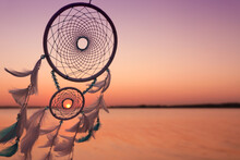 Beautiful Handmade Dream Catcher Near River At Sunset. Space For Text