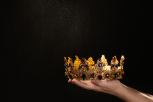 Woman Holding Beautiful Golden Crown On Black Background, Closeup With Space For Text. Fantasy Item
