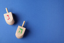 Hanukkah Traditional Dreidels With Letters Gimel And He On Blue Background, Flat Lay. Space For Text