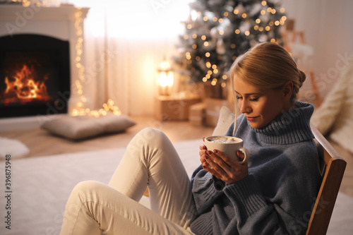 Photo Young woman with cup of hot drink at home, space for text