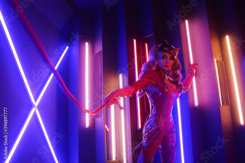 Canvas Sexy young woman in leather red dress with cat mask in neon lights