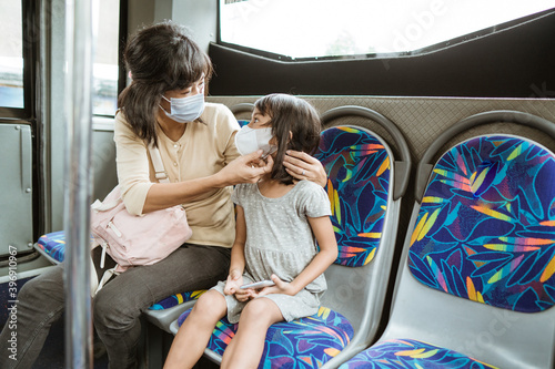Tablou Canvas mother and daughter riding public transport during pandemic wearing facemask