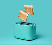 Bread Popping Up Of Toaster On Mint Green Background