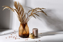 Home Improvement And Decoration Concept - Still Life Of Decorative Dried Flowers In Brown Glass Vase, Candle And Pumpkin