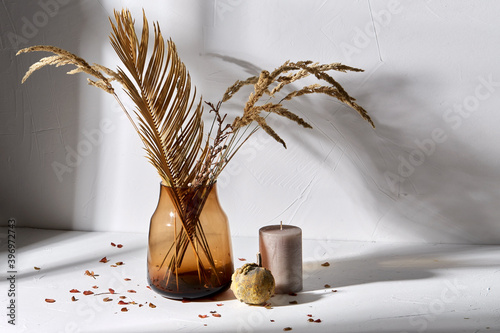 Fototapeta home improvement and decoration concept - still life of decorative dried flowers in brown glass vase, candle and pumpkin obraz