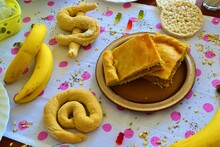 Wooden Brunch Table With A White Tablecloth With Pink Polka Dots, Empanada, Bananas, Rice Cakes, At Sign Or Dollar Symbol Breads, Gummy Bears And Oat Flakes