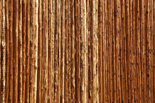 The High Dense Fence Is Made Of The Pine Logs Cleared Of Bark. Original Background.