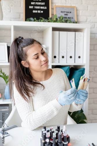 Fotografering Manicure master in gloves working in nail salon holding various plastic nails ti