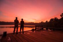 LAKE YEAK LAOM, BAN LUNG DISTRICT, RATANAKIRI, CAMBODIA - 08 December 2009: Couple Watch Beautiful Sunset Over Volcanic Crater Lake.