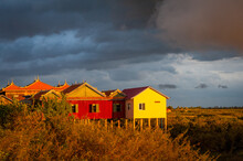 SUNSET, UDONG, CAMBODIA - 15 July 2012: Brightly Coloured Houses Catch Sun In Dramatic Sunset With Cloudy Sky.