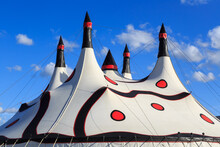 A White Big Top Circus Tent, With Many Spires And A Pattern Of Red Dots And Black Swirls