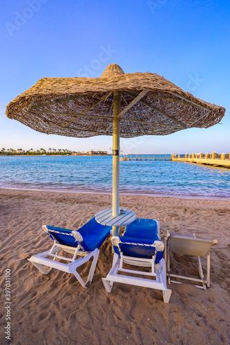 Relaxing at paradise beach - Chaise lounge and parasols - travel destination Hur Fototapeta