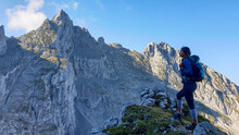 A Woman With A Backpack Standing In The Shadow At The Mountain Peak And Enjoying The View On Higher, Very Steep Peaks In Front Of Him. Way To The Grimming In Austrian Alps. Freedom And Exploration