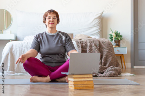 Fototapeta Senior woman meditates at home in a lotus position in front of a laptop monitor. The concept of a healthy lifestyle in old age. obraz