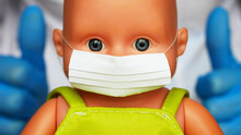 Close-up Of A Baby Doll With A Protective Face Mask Against Doctors Hands Background
