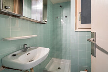Old And Dirty Bathroom With Faucet, Shower Zone And Blue Tiles In An Old House Of Barcelona