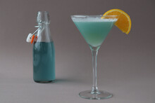 Composition Of Blue Lagoon Cocktail Decorated With A Slice Of Orange With A Bottle On Grey Background