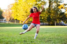 Latin Female Soccer Player Kicking Ball