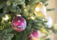 Original Christmas Photograph Of A Golden Christian Nativity Scene On A Burgundy And Gold Christmas Ball Ornament Hanging On The Christmas Tree.