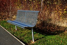 Modern Silver Coloured Metal Park Bench On A Late Autumn Day.