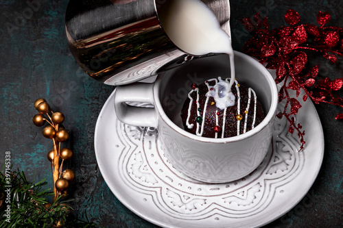 Fototapeta Cocoa bomb that melts with hot milk. Cup of dark hot chocolate. Milk splash. Comfort food. White wood table with green cloth and golden spoon.Christmas treat. obraz