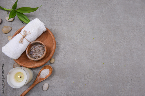Vászonkép Rolled towels and salt spoon in bowl in wooden bowl, bamboo leaves,stone and,can