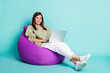 canvas print picture - Photo portrait full body view of girl working on laptop sitting in purple beanbag armchair isolated on vivid teal colored background