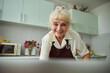 Leinwandbild Motiv Lovely old woman in apron standing in kitchen