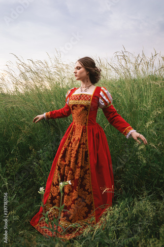 beautiful young woman in a long red medieval dress is standing in the grass in the field under the cloudy sky, fantasy princess