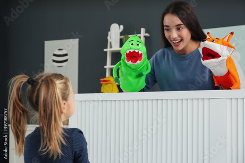 Fototapeta Mother performing puppet show for her daughter at home