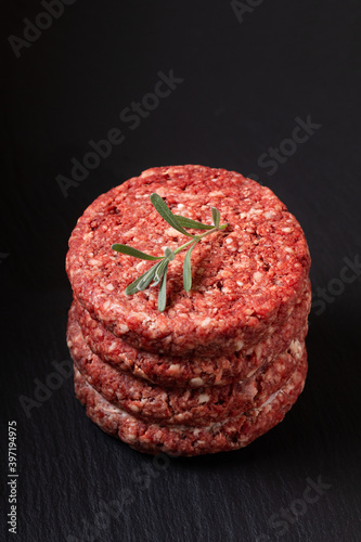Food Concept Ground beef or hamburger beef patty stack on black slate board with Fototapet