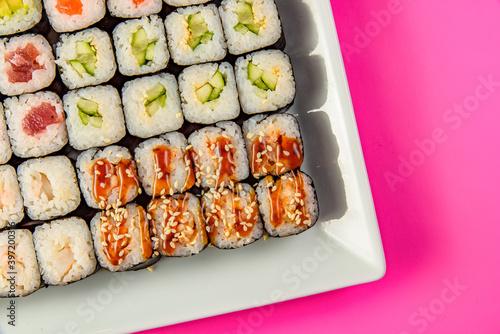 Fototapeta Mix of Japanese maki nori rolls in on a pink background obraz