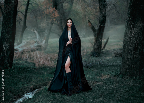 Obraz Mysterious fantasy gothic woman dark witch obsessed by evil. Girl demon vampire in black dress cape hood. walk in dark dense deep forest background, trees. Medieval queen in silk cloak, scarf posing - fototapety do salonu