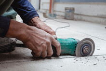 A Construction Worker Uses An Angle Grinder To Cut A Line Into The Concrete Floor. Creating A Tile Pattern On The Surface. Held With Bare Hands.