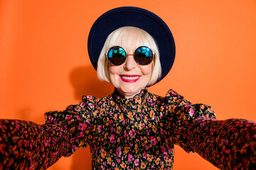 Portrait of happy smiling cheerful positive grandmother take selfie wear sunglasses isolated on orange color background