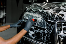 Close Up Photo Of Hands Of Auto Service Male Worker In Black Protective Gloves Cleaning Car Hood And Headlights With Foam And Soft Brush. Carwash And Detailing.