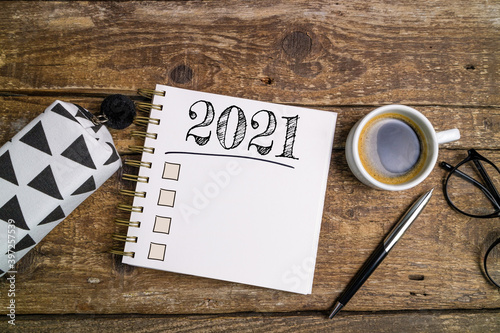 New year goals 2021 on desk. 2021 resolutions list with notebook, coffee cup and eyeglasses on wooden background. Goals, plan, strategy, business, idea, action concept. Top view