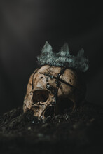 Spooky Human Skeleton Skull With Weathered Crown Placed On Pile Of Ash Against Black Background