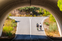 Full Length Back View Of Distant Unrecognizable Bicyclists In Sportswear And Helmets Cycling Together On Asphalt Roadway Under Arched Bridge In Summer Countryside