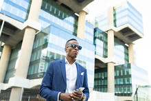 From Below Black Male Entrepreneur Wearing Formal Suit And Sunglasses Standing Near Glass Office Building Looking Away