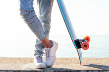 Unrecognizable Stylish Skater In Jeans And Sneakers Standing Next To Skateboard On Street On Sunny Day In Summer