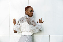 Crop Of Back View Of Confident Young Slim African American Female In Stylish Blouse And Pants Standing Against Wall Of Modern Building And Looking At Camera