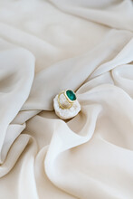Delicate Ring With Precious Green Gem Placed On Piece Of White Quartz On Soft Bed
