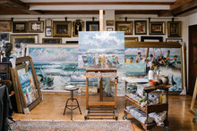 Interior Of Creative Art Workshop With Painting On Easel Near Shelf With Tools And Variety Of Ready Framed Pictures