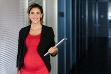 Cheerful Pregnant Female Office Worker Standing With Tablet In Workplace And Looking At Camera