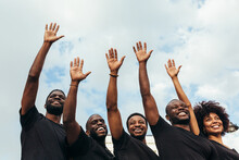 Cheerful Black Men And Woman Raising Hands Against A Blue Sky