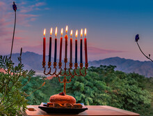 Burning Candles, Menorah And Sweet Donates On Plate With Wooden Dreidels For Hanukkah Holiday - Hebrew Letters On Side Of Dreidel Means - Great Miracle Happened Here. Blurred Morning Sky And Mountains