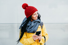Smiling Woman Looking Away While Using Smart Phone Standing Against Wall During Autumn